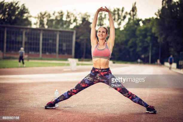 spreading legs and warming up hips on outdoor training - women spreading their legs stock photos and pictures