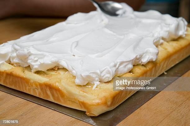 Spreading meringue smoothly on apple cake