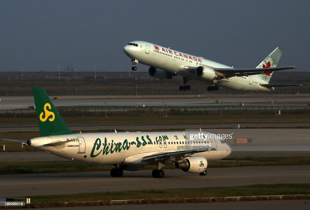 A Spring Airlines Co. aircraft, bottom, taxies as an Air Canada aircraft takes off at Shanghai Pudong International Airport in Shanghai, China, on Saturday, Oct. 26, 2013. Airline profits worldwide in 2013 will be 7.9 percent smaller than estimated at $11.7 billion amid sluggish travel demand and rising oil prices tied to the Syria crisis, the International Air Transport Association said last month. Photographer: Tomohiro Ohsumi/Bloomberg via Getty Images