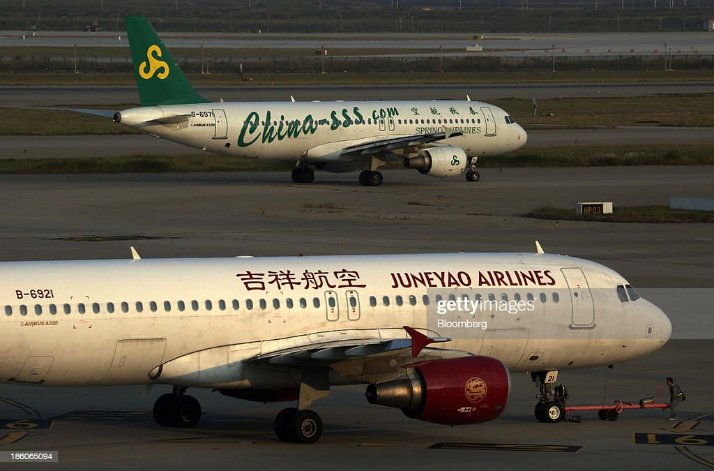 A Spring Airlines Co. aircraft, top, and a Juneyao Airlines Co. aircraft taxi on the tarmac at Shanghai Pudong International Airport in Shanghai, China, on Saturday, Oct. 26, 2013. Airline profits worldwide in 2013 will be 7.9 percent smaller than estimated at $11.7 billion amid sluggish travel demand and rising oil prices tied to the Syria crisis, the International Air Transport Association said last month. Photographer: Tomohiro Ohsumi/Bloomberg via Getty Images