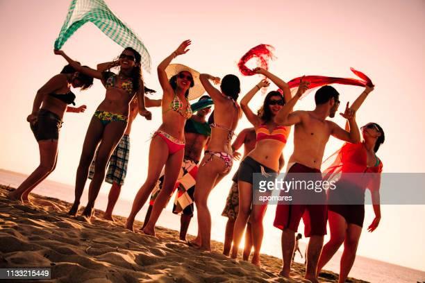 Spring Break rétro-éclairé groupe de jeunes gens dansant sur la plage