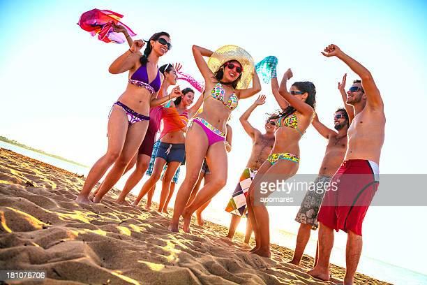 春休みバックライト若者のダンスグループのビーチ
