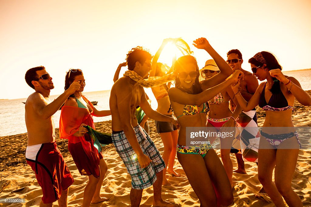 Spring break backlit group of young people dancing on beach : Stock Photo