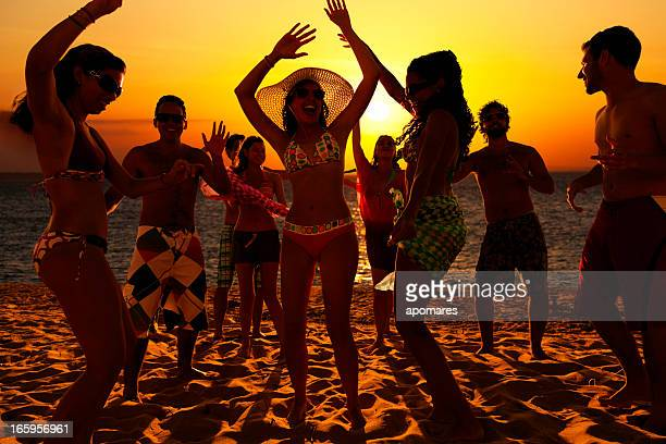 Spring break group of young people dancing on a beach