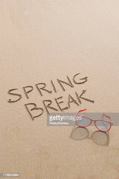 Vacances de printemps des lunettes de soleil sur le sable