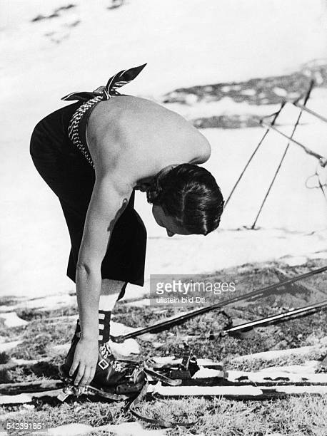 Spring fashion at the Arlberg woman with lowbacked shirt putting on her skis Photographer Lothar Ruebelt 1936Vintage property of ullstein bild