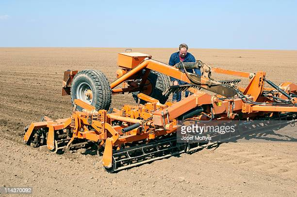 spring field with cultivator - tiller stock photos and pictures
