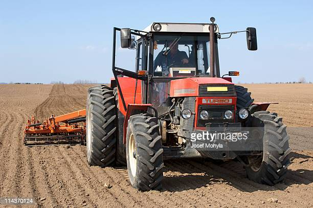 spring field with tractor and cultivator - tiller stock photos and pictures