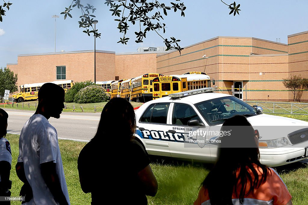 Spring High School parents wait across the street from Spring High School for their children to be released from a lockdown after a stabbing at the school September 4, 2013 in Spring, Texas. A 17-year-old student was fatally stabbed and three other students during what has been reported as a fight at the school about 7:00 am. Three people have been taken into custody.