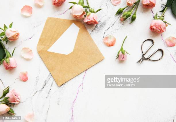 spring holiday theme, roses and letter on a white marble background - marmo bianco foto e immagini stock