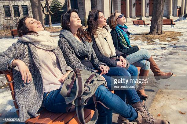 Spring is finally here! Four girls on a bench park.