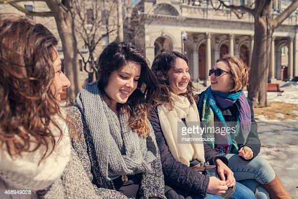 """spring is finally here! four girls on a bench park. - """"martine doucet"""" or martinedoucet stock pictures, royalty-free photos & images"""