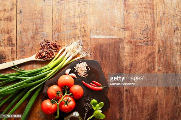 spring onions, red tomatoes,chillies and other spices on wooden table - wood material stock pictures, royalty-free photos & images