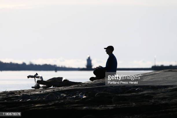 Spring Point Ledge Light looms in the background while Ezra Silk of Portland practices mindfulness and loving kindness mediation on East End Beach...