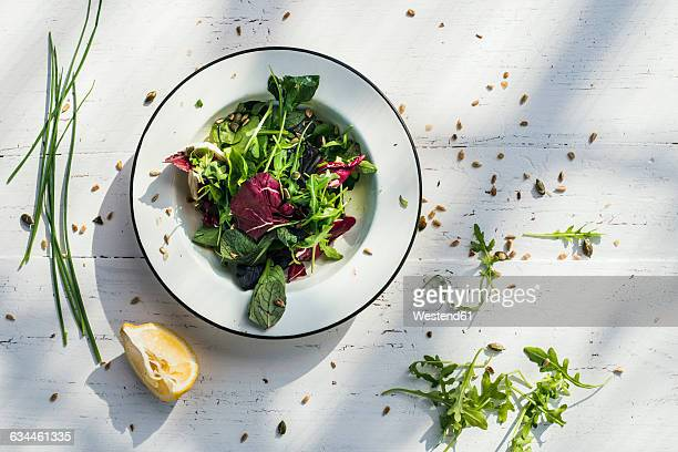 spring salad of baby spinach, herbs, arugula and lettuce on plate, lemon - lettuce stock pictures, royalty-free photos & images