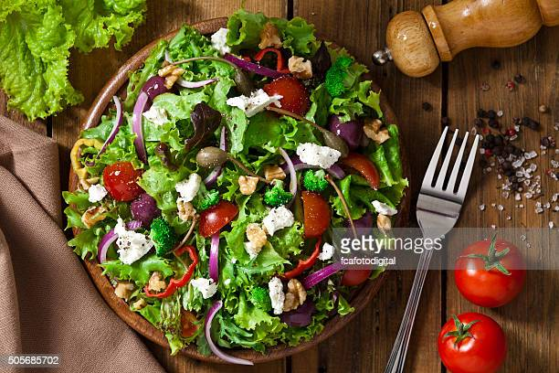 spring salad shot from above on rustic wood table - nut food stock photos and pictures