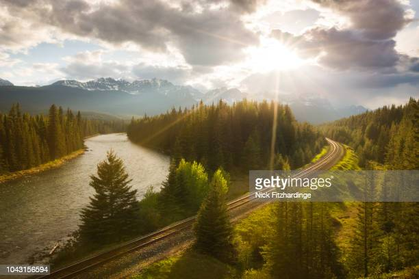 spring sunshine over the railway tracks in the canadian rockies, banff national park, alberta, canada - bahngleis stock-fotos und bilder