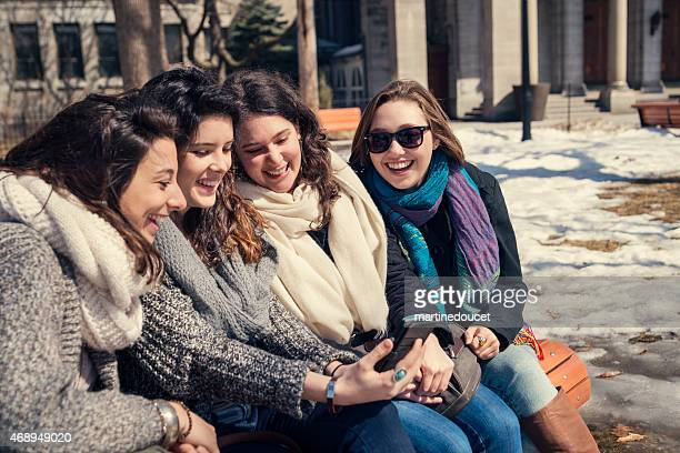 """spring time! girls on bench park looking at mobile phone. - """"martine doucet"""" or martinedoucet stock pictures, royalty-free photos & images"""