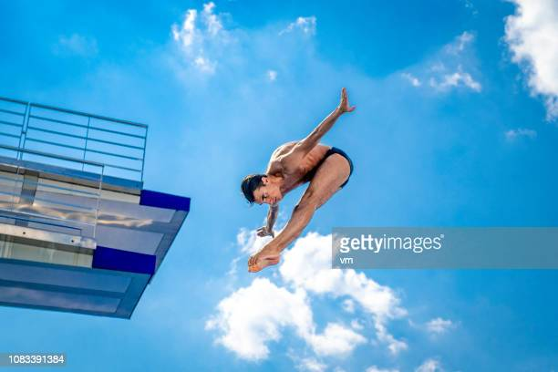 springboard diver in mid-air - diving board stock pictures, royalty-free photos & images