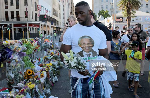Springbok Rugby player Siya Kolisi leaves flowers for Nelson Mandela at the Grand Parade on December 8 2013 in Cape Town South Africa Yesterday...