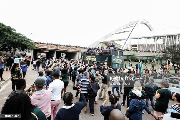 Springbok supporters celebrate while the South African Rugby World Cup winner team parade passes the Moses Mabhida Soccer Stadium on an open top bus...
