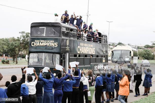 Springbok supporters celebrate while the South African Rugby World Cup winner team parades through Kwamashu township on an open top bus showing the...