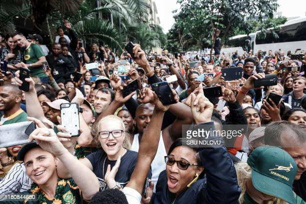 Springbok supporters celebrate while the South African Rugby World Cup winner team parades through the Durban CBD on an open top bus in Durban on...