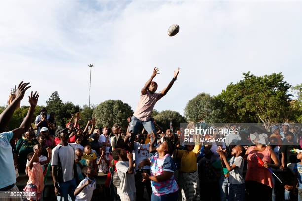 TOPSHOT Springboks supporters make a mock lineout as they wait for the national rugby team to parade the Web Ellis Cup at the Hector Pieterson Museum...