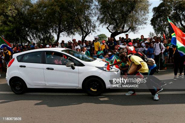 Springboks supporters make a mock scrum against a passing vehicle as they wait for the national rugby team to parade the Web Ellis Cup at the Hector...
