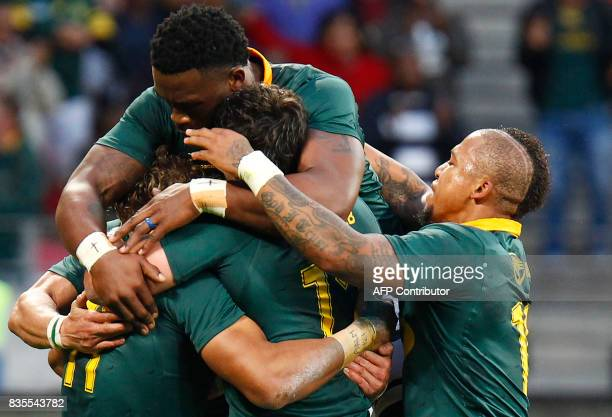 Springboks winger Courtnall Skosan is mobbed by teammates as he celebrates scoring a try during the International Rugby Test match between Argentina...