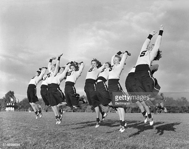 Springfield High School cheerleaders jump and cheer while performing on a sports field Delaware County Pennsylvania March 5 1941