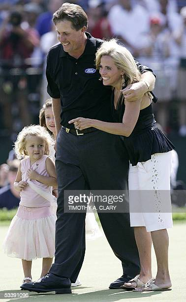 Springfield, UNITED STATES: Phil Mickelson of the US celebrates his winning putt with his wife Amy and his children on the 18th green at Baltusrol...