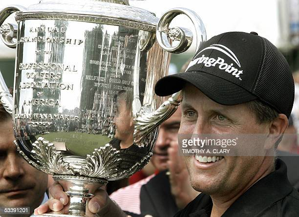 Phil Mickelson of the US holds up the Wannamaker Trophy after winning the 87th PGA Championship at the Baltusrol Golf Club in Springfield NJ 15...