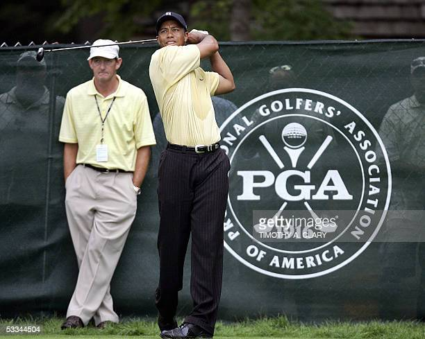 Springfield, UNITED STATES: Tiger Woods of the US tees off on the 13th hole as his swing coach Hank Haney looks on during the practice round for the...