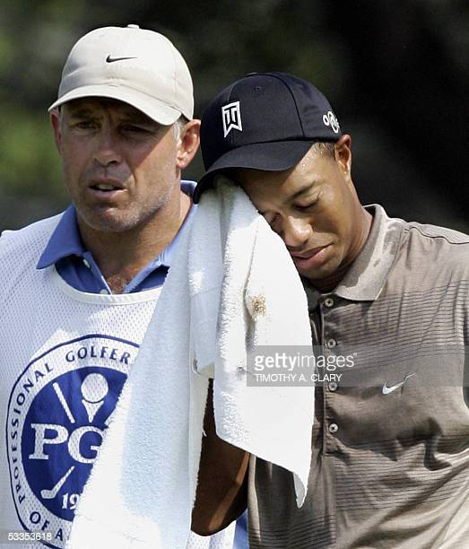 Springfield, UNITED STATES: Tiger Woods of the US wipes his head as his caddie Steve Williams points out his putt during the first round of the 87th...