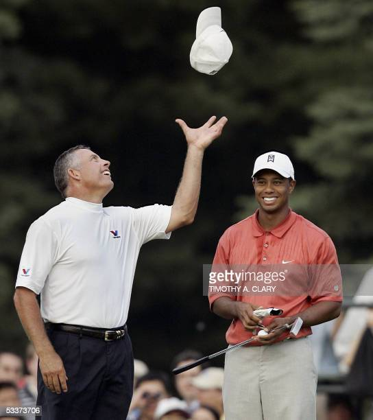 Springfield, UNITED STATES: Tiger Woods smiles as his caddie Steve Williams throws his hat in the air on the 18th green after Woods finished at...