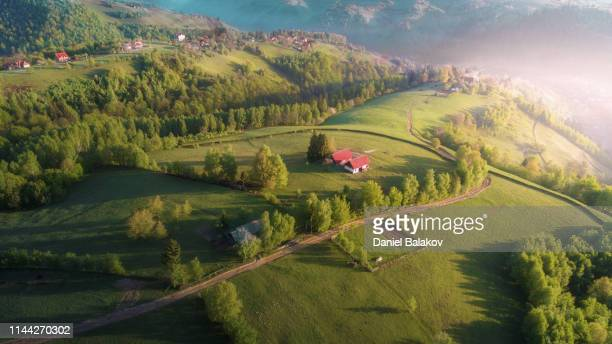 springtime. aerial view over transylvania green fields, mountain village at sunrise, bright sunlight, small houses, springtime, greenery, carpathian mountains, majestic view, travel destinations - romania stock pictures, royalty-free photos & images