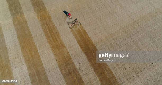 Springtime agricultural activity, red tractor cultivating field