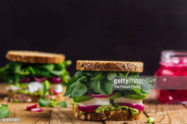 Springtime feta sandwiches with avocado, pickled red onions and herbs like arugula, purslane and fresh mint served on a wooden board