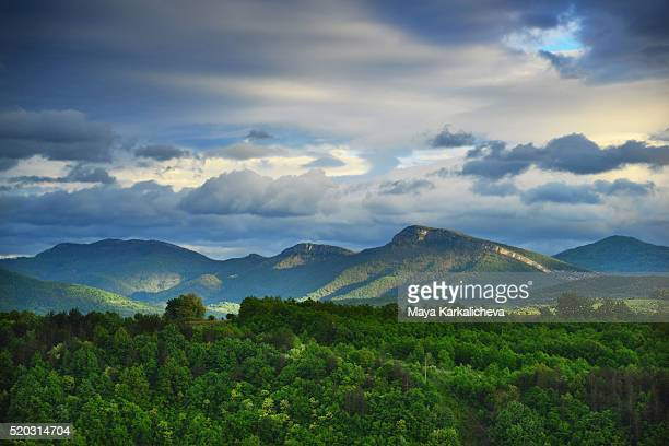 Springtime mountain panorama with a dramatic sky