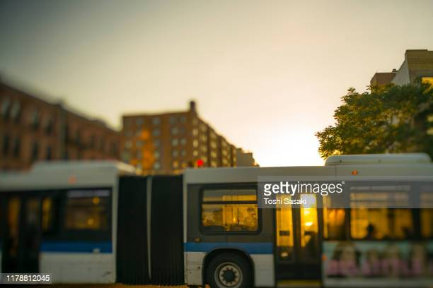 springtime sunset light among the rows of buildings, which illuminates the bus crossing the houston street in new york city ny usa on may. 18 2019. - ヒューストンストリート ストックフォトと画像