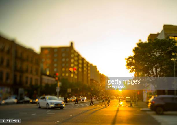 springtime sunset light among the rows of buildings, which illuminates the buildings, cars and people on the houston street in new york city ny usa on may. 18 2019. - ヒューストンストリート ストックフォトと画像