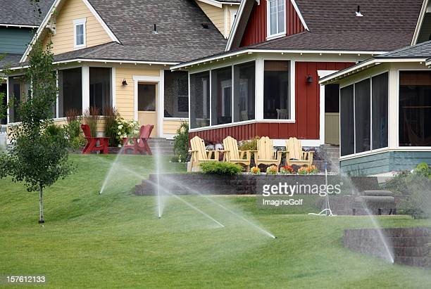 sprinkler system in a pretty residential community - irrigation equipment stock pictures, royalty-free photos & images