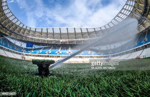 A sprinkler waters the pitch of Volgograd Arena in Volgograd on May 9 2018 The nearly 45000seater stadium will host four World Cup matches