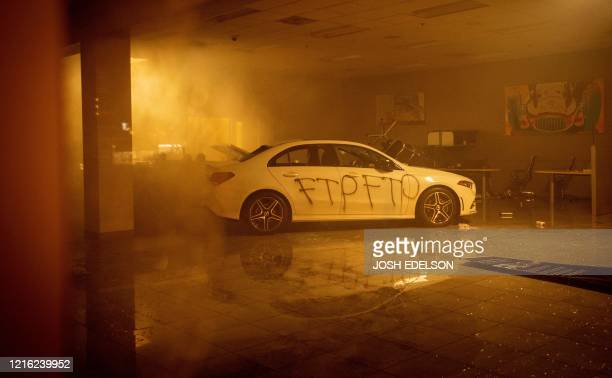 Sprinklers and smoke fill the air at a vandalized MercedesBenz dealership in Oakland California on May 30 over the death of George Floyd a black man...