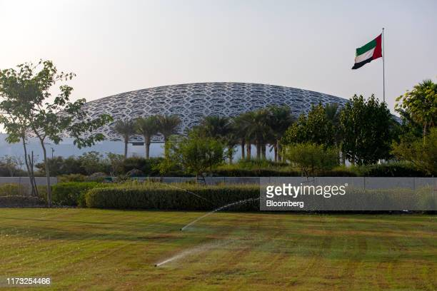 Sprinklers water a grass lawn outside the Louvre Abu Dhabi museum on Saadiyat Island in Abu Dhabi, United Arab Emirates, on Wednesday, Oct. 2, 2019....
