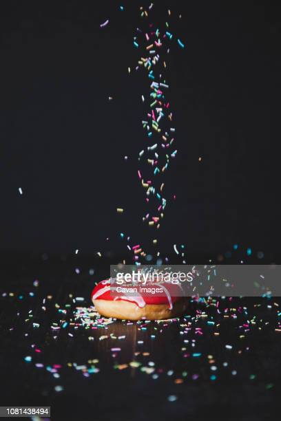 sprinkles sprinkling on donut at wooden table against black background - sugar sprinkles stock pictures, royalty-free photos & images