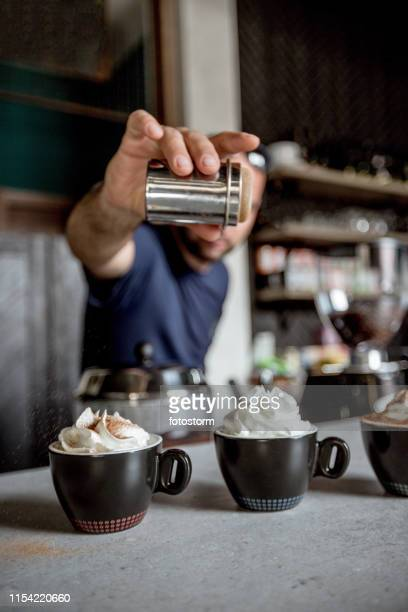 sprinkling cinnamon on mocha coffee - mocha stock pictures, royalty-free photos & images