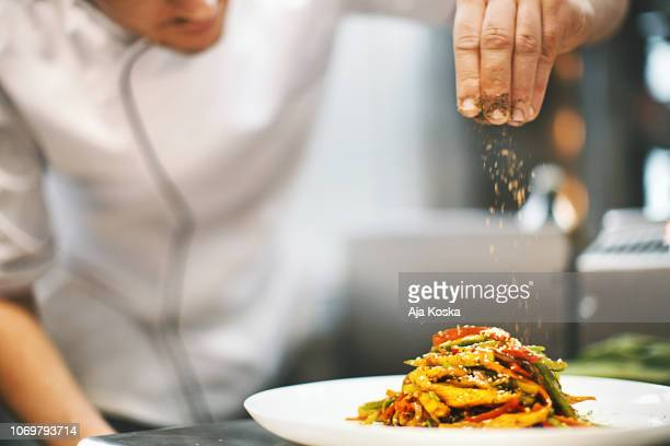sprinkling seasonings from high up. - restaurant stock pictures, royalty-free photos & images
