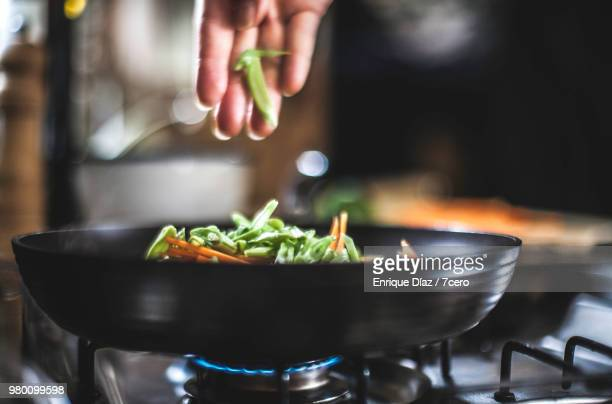 sprinklinging shredded vegetables in a pan for korean pancakes. - cooking pan stock pictures, royalty-free photos & images